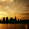 <h2>Two Suns - The New York City Skyline at Sunset</h2> - By Vivienne Gucwa  Before the night trails across the sky leaving darkness and whispers in its wake, the sun melts over the city's towering silhouettes pouring its essence into the water like liquid gold.  The city lights illuminate the urban landscape like stars while each and every last ember of daylight fades: extinguished sparks exhaled in the long sighs of evening wanderers.