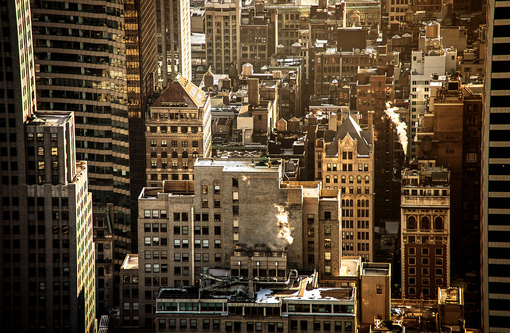 <h2>New York City Rooftops - From Above - Midtown Skyscrapers</h2> - By Vivienne Gucwa   These are the skyscrapers of midtown Manhattan from above as seen from the top of Rockefeller Center (Top of the Rock). Looking out over these time and weather-worn buildings, it's almost incredible to think of the sheer amount of activity occurring behind each tiny-eyed window at any given time.  This is a scene that peaks in the teasing warmth of winter sunlight as the sun dips towards the horizon in the late afternoon. With  rooftops covered with a light glaze of snow and with sultry exhales of smoke billowing out into the late afternoon sunlight, the city basks momentarily in distant memories of summer.   When I was younger, I used to imagine how incredible it would be to fly through the city like Batman. I would close my eyes and imagine dipping into the dark,narrow valleys created by tall skyscraper peaks. I would ascend up past the multitudes of water towers to distant rooftops where I would bide my time while seeking out other routes to glide through (in my imagination Batman took quite a few joyrides through the city!).   I still like to imagine these things. It's probably why I love views that take me above the hustle and bustle of the city. There is a peace that seems to come with viewing the cityscape from above.   ---