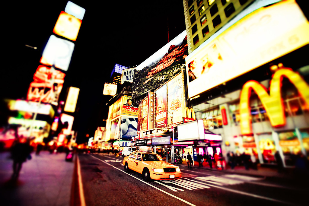 <h2>Times Square - New York City</h2>- By Vivienne Gucwa  Times Square is its own universe. It's New York City filtered through cinematic dreams and commercially-tinged aspirations wrapped up in flashing lights and colorful billboards. There is a familiarity to it that is tinged with a wild-eyed estranged quality that makes it all the more alluring.   And when a yellow New York City taxi cab drives by at the speed of light under all the flashing lights, it's hard not to smile.  ---