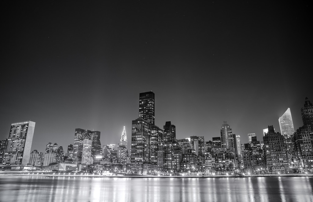 <h2>New York City - Night </h2> - By Vivienne Gucwa<br><br>  I have been traipsing all over the city for the last few months trying to capture a large majority of New York City's skyline views. I think everyone has a particular skyline view they immediately think of when they think of the city. And yet, it's still incredible to me after all this time that I come across different skyline angles that I hadn't previously come across or had the time to explore before from certain vantage points.<br><br>  New York City has several prominent skyline views that are popular. One is in lower Manhattan and usually includes the skyscrapers of the Financial District along with the one or more of the bridges that serve the lower part of Manhattan. The other series of skyline views can be found from the top of a few popular skyscrapers in midtown Manhattan. Another series of skyline views involves the midtown Manhattan skyline as seen from different vantage points across (or in some cases directly from) the East River. This particular view is taken from one of the latter vantage points. It's a 30 second long exposure taken on a gorgeously clear and cold night in the beginning of March from Roosevelt Island.<br><br>  Prominent skyscrapers in this view are the Chrysler Building and the United Nations building (all the way to the left). The lights of other famous midtown skyscrapers can also be seen even if those skyscrapers (looking at you Empire State Building) are hidden in this view. The lights directly in front of the skyscrapers that line the East River belong to the FDR Drive, a major traffic route that lines New York City's east side.<br><br>  --------<br><br>