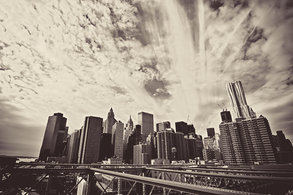 <h2>Steel Arteries - The New York City Skyline Viewed from the Brooklyn Bridge</h2> - By Vivienne Gucwa  If the Brooklyn Bridge and New York City have been engaged in a reciprocal love affair for decades. It's hard to argue that the Brooklyn Bridge's heart isn't completely devoted to New York City.  Its steel arteries all seem to lead away from its center towards the magnificent skyline that dominates lower Manhattan while its metal veins travel from Brooklyn to its very core.