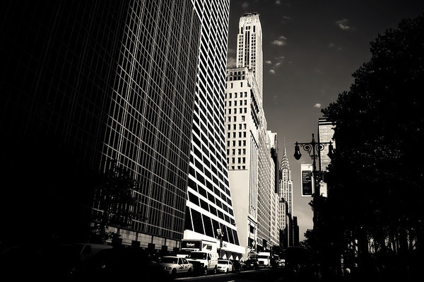 The W.R. Grace Building and the Chrysler Building - Midtown - New York City - By Vivienne GucwaThere are certain views in the city that seem to have embedded themselves in my mind over time. This view, is one of those types of views. When I think of some of the first times I noticed the Chrysler Building when I was much younger, this is the view that immediately springs out of the recesses of my memory. I can't quite remember the first time I took in this view but I also can't remember viewing the Chrysler Building from any other vantage point when I think back on my first impressionable views of the iconic art deco masterpiece of architecture. It's as if this portion of the city didn't exist until I saw it in this exact way as if once I laid eyes on this scene, my mind dream-sketched it into existence.Perhaps that's how we all form our own significant impressions of our surroundings. The memorable bits inhabit a place in our minds where they can spring forth when thinking of a certain place: a treasure chest of imagery that sits in our minds waiting for us to open it with our eyes.---This particular view is adjacent to Bryant Park on 42nd Street. The sloped building in the foreground is the W.R. Grace Building which was designed by Gordon Bunshaft and completed in 1974. When I was little I used to imagine how awesome it would be to slide down the facade of the building. It turns out, I wasn't the only one who imagined such a thing. In 2007, the Grace Building was featured in the 2007 Marvel Comics motion picture Fantastic Four: Rise of the Silver Surfer. The Silver Surfer, pursued by the Human Torch, surfs down the south face of The Grace Building, imploding windows in his cosmic-energy wake.---