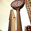 <h2>Flatiron Building and 5th Avenue Building Clock - New York City</h2> - By Vivienne Gucwa  I have always loved the ornate clocks that line 5th Avenue, especially the Fifth Avenue Building Block that has a prime destination near the Flatiron Building. At 19 feet high, the cast-iron clock was installed in 1909 was made by a Brooklyn Iron Works company. It's a type of clock that was introduced in the 1860s. They were popular with business owners who wanted to attract extra attention and also served a functional purpose as time-telling pieces in a busy area of Manhattan.  The juxtaposition between the Flatiron Building, one of New York City's iconic skyscrapers and this cast-iron clock has always put a smile on my face. The Flatiron Building, which was completed in 1902 is also a landmark in Manhattan. Its name is in reference to its resemblance to a cast-iron clothes iron.  ---