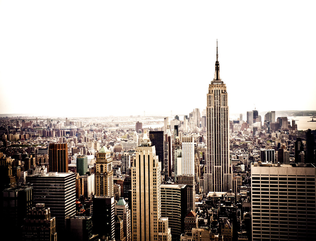<h2> The New York City Skyline and the Empire State Building</h2> - By Vivienne Gucwa  Rising up from the density of the urban landscape, giant stalagmites formed by the downward flow of steel and concrete from somewhere high up in the clouds assert their presence.  Reaching towards the dizzying heights where dreams reside, these monoliths guide all city dweller's dreams upward like lighthouses in an urban sea.  ---