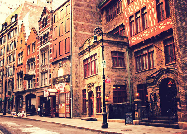 <h2>Stone Street Historic District - Financial District - New York City </h2> - By Vivienne Gucwa  Something I absolutely love about New York City is that tucked away between the towering monuments of modernity that populate the cityscape are streets that look as if they have been transported from another era and geographic location entirely. These streets are suspended in time like flies in amber.  This area is known as the Stone Street historic district in lower Manhattan. Bound by Stone Street, Pearl Street, and South William Streets and Mill Lane, it is a section that is unlike any of its surrounding blocks. This particular section is bound by South William street and 13-15 South William Street can be seen in this particular view. Around the block from this part of the area are other historic buildings and the Stone Street area 'proper'.  In 1903, the architect C.P.H. Gilbert designed new street facades on the buildings in this section of South William Street (57 Stone Street on the other side). Gilbert's neo-Dutch Renaissance architecture features structural details like stepped gables and strapwork and was a nod to the early settlement of Manhattan .  This area which dates back to the 1600s when New York City was first colonized by Dutch settlers was sadly destroyed by the Great Fire of 1835. The surrounding section of Stone Street was rebuilt with granite bases of post-and-lintel construction and upper-additions of brick which were specifically erected for importers and merchants.  ---