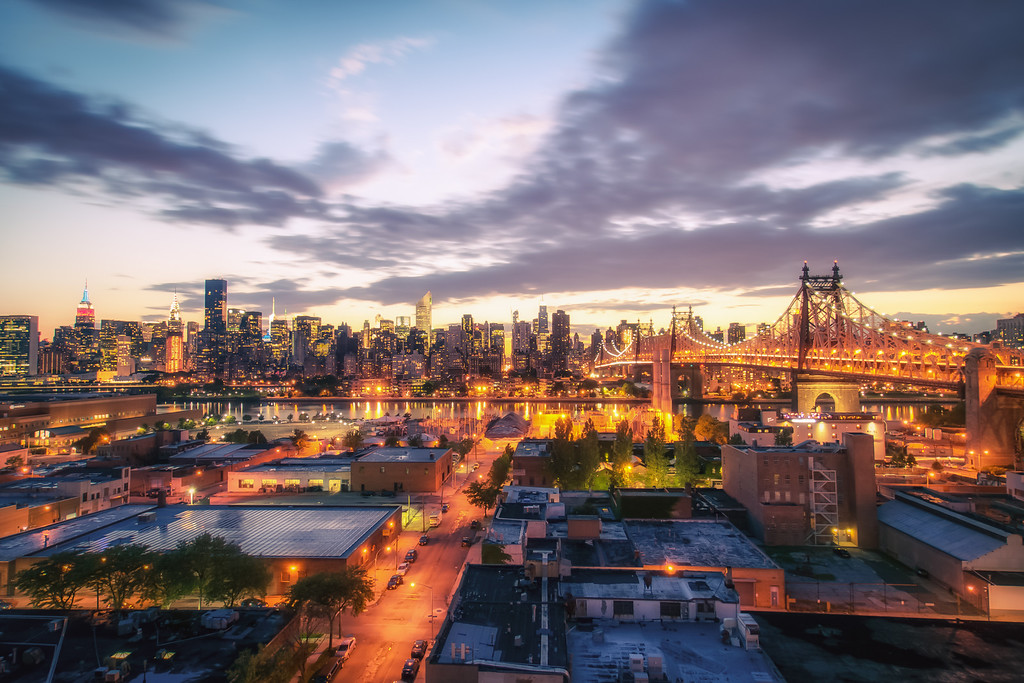 <h2>New York City Skyline and Long Island City Rooftops</h2> - By Vivienne Gucwa<br><br>  There is something so magical about dusk in New York City. <br><br>  After the sun sets for the evening, the city is a symphony of lights reaching their crescendo at the same time as the night pulls itself over the rooftops and skyscrapers below. <br><br>  And if you squint just a little, <br><br>  all of the lights twinkle <br><br>  like fireflies in an urban forest. <br><br>  ---<br><br>  This is a 15 second exposure taken while standing on the roof of Z Hotel in Long Island City, Queens. The rooftops of Long Island City sit in the foreground. To the right is the Queensboro Bridge (also known as the 59th Street Bridge, and the Ed Koch Queensboro Bridge). The skyline of midtown Manhattan including the Empire State Building and the Chrysler Building sit in the distance. <br><br>  ---<br><br>