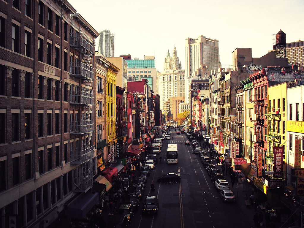 <h2>Heart of it All - Above Chinatown - New York City</h2> - By Vivienne Gucwa  This is one of my favorite views of Chinatown. The view is of East Broadway, a main street in Chinatown that extends into the Lower East Side. A girl sits on one of the rooftops eating a bowl of food in the upper right hand corner of this photo. The Municipal Building sits in the distance.  This particular spot is a Chinatown neighborhood known as 'Two Bridges'. Two Bridges sits along the East River and has long been a dwelling spot for many different immigrant communities over the years. It sits alongside the infamous and historic Five Points area where Irish, Jewish and Italian gangs battled to the death in the mid-19th century. It is currently home to a large community of Chinese immigrants and many of the buildings are tenements dating back to the late 19th and early 20th centuries.  ---