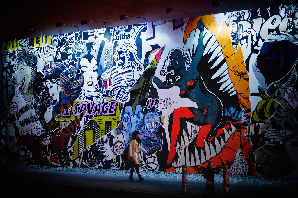 <h2>Night Visions - Street Art - East Village - New York City</h2> - By Vivienne Gucwa<br><br>    When I was really young, I used to imagine that at night when the majority of people went to sleep in New York City, all of the graffiti and street art on the walls would come to life. Every figment of an artist's imagination, previously bound to the confines of a wall, would finally get to roam the city streets with abandon.<br><br>  I still like to think this is the case. While reality is never quite as vivid as my imagination, the magic of photography keeps those sorts of dreams alive. I remember waiting in front of this mural for a long time at night for the right person to breathe life into the scene. <br><br>  As the star of the cinematic scene in my mind approached, I couldn't have been happier. She walked onto this colorful urban set and it was as if she had merely leaped out of the mural only moments before. <br><br>  --- <br><br> This colorful street art collage of pop culture and comic book inspired figures once graced a wall on the corner of Houston and the Bowery in the exciting neighborhood of the East Village in New York City.<br><br>