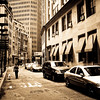 "<h2>Dog Walking - Financial District - New York City </h2> - By Vivienne Gucwa  I have been thinking a lot about different visions of New York City a lot lately. I had an interesting interview for a project I am being considered for a few weeks ago where I found myself talking about what I try to convey about New York City with my photography and writing.  It was interesting to talk about it face to face (over Skype) rather than write about it because in a sort of stream of consciousness way I had to explain to someone who had never been to New York City how I try to show how I experience New York City on a regular basis via my own views of it colored by falling in love with a combination of streetscapes in classic film noir cinema, futuristic sci-fi city environments in literature and film, and years of traversing New York City on foot.   A few nights ago, I watched a documentary about Woody Allen and there was a segment in it that resonated with me deeply which is no surprise since I am a huge fan of the Annie Hall and Manhattan era Woody Allen films. Martin Scorcese, the director of masterpieces such as: Mean Streets, Taxi Driver, Raging Bull, Goodfellas and Gangs of New York talks about Woody Allen's extreme nostalgia for the present that is evident in Allen's film Manhattan. He states that for Woody Allen it is as if New York City is constantly alive and continually evolving but Allen's New York City is an entirely different planet from his own. The documentary switches over to Woody Allen who then states: ""I wanted to show New York in a very beautiful way, the way I see it. I never had any interest in showing it except through my rose colored glasses; my romanticized view of it.""   There is definitely a romanticized element that is evident in my photography of New York City. When I walk from my apartment on the Lower East Side through Chinatown and Soho or up through the East Village towards midtown, I am bombarded with memories and desire to capture the fragments of life and architecture that, for me, tug at the visions of New York City I have in my own mind. I hope that one day if and when I have the means to travel I will be able to do the same which each place I explore and experience.  ---"