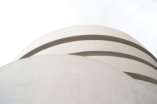 <h2>The Solomon R. Guggenheim Museum - New York City</h2> By Vivienne Gucwa  Sometimes the simplicity of a scene is enough to render one speechless before realizing that the perceived simplicity is complex in its own right.  The curves of architecture suggesting a softness usually relegated to flesh against a bone white sky, for example.  The architecture in this photo is the work of Frank Lloyd Wright and is the top of the Solomon R. Guggenheim Museum. Wright was commissioned to design a space for the museum in 1943 and the project took well over a decade to complete. He apparently was disappointed in the choice of New York City as the home of the building as he thought that New York City was overbuilt and overpopulated. However, he complied with the wishes of the client and the Guggenheim was set to be built next to Central Park as possible to keep it as close to nature as possible. It is located on the Upper East Side on 5th Avenue between 88th and 89th Streets across from Central Park.  ---  ---