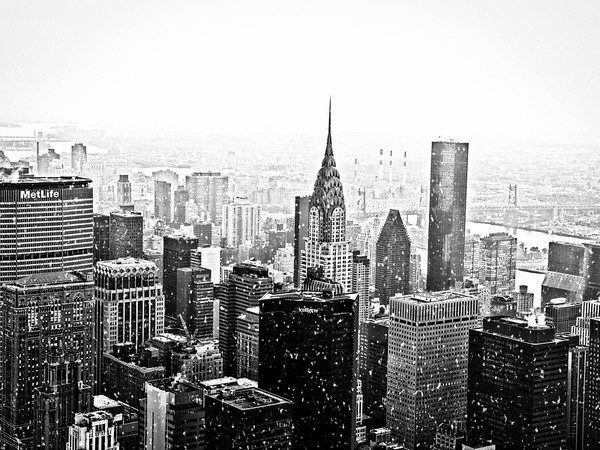 <h2>New York Winter - Snow Over the New York City Skyline</h2> - By Vivienne Gucwa  Snowflakes swirl over the skyscrapers and buildings: confetti from the sky blanketing the buildings and streets.  And the world transforms into a giant snow-globe, if only for a brief moment.  ---  What's more magical than New York City in the snow (when it first falls, of course)? This winter cityscape view is of the skyscrapers of the New York City skyline in midtown Manhattan including the Chrysler Building, the MetLife Building and a barely visible 59th Street Bridge (also known as the Ed Koch Queensboro Bridge).   ---