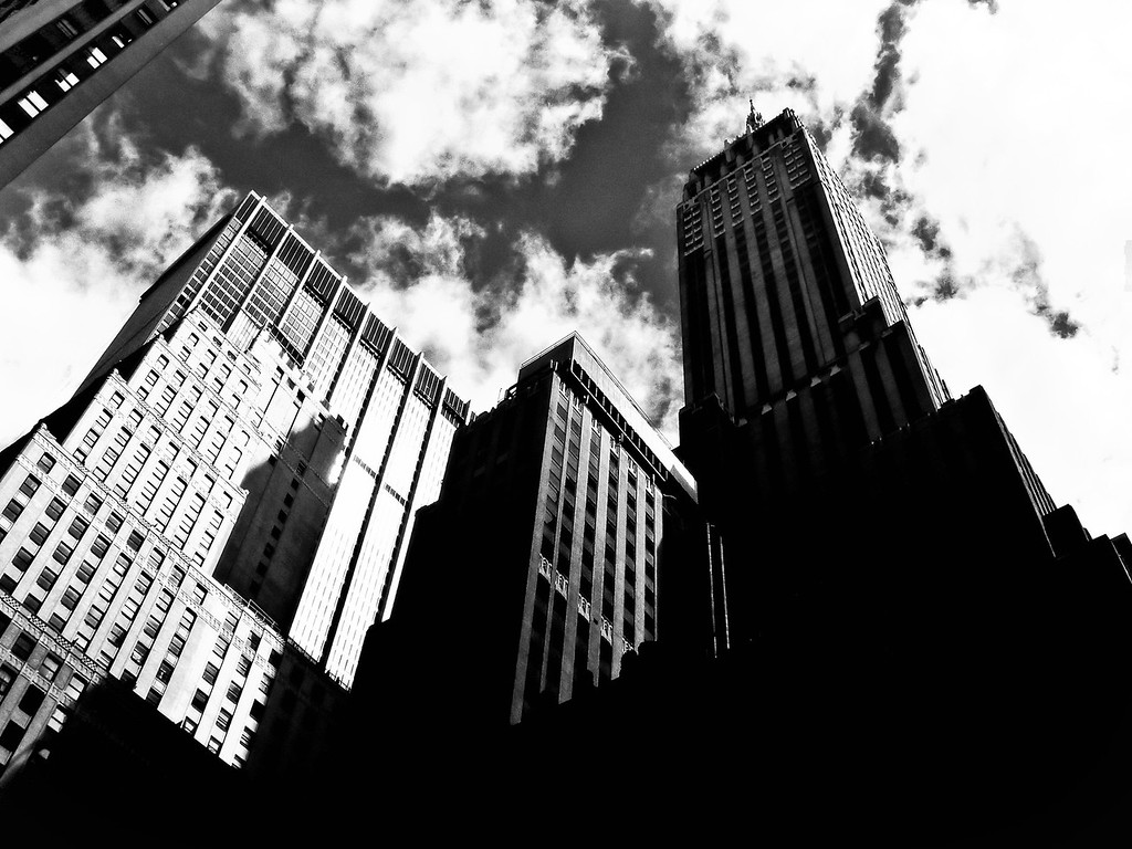 "<h2>Enchantment - Skyscrapers - Financial District - New York City</h2> - By Vivienne Gucwa   When I was very young, I remember learning about vast mountain ranges that existed in what seemed like universes beyond New York City. I would regale myself with images of these towering feats of nature trying to imagine what it was like to come in contact with such powerful natural wonders. I used to think to myself ""There is nothing like this here in the city, all we have are buildings.""   It wasn't until my teens when I lived in New Mexico for a little over a year and more specifically when I got to experience the majesty of Taos that I was able to understand how infinitely small everything seems in comparison to the vastness of the world.   And yet, while I was in school there in Albuquerque, other students would ask me daily to tell them what it was like to live amongst buildings that soared to the sky.  It never occurred to me before that time that the man-made feats of architecture that I viewed on a regular basis were for these students what the images of mountain ranges were to me before I had the experience of seeing mountains with my own eyes.  When I moved back to New York City, I carried that new knowledge with me like a precious gift, tucking it away for safe-keeping.  And it wasn't until I discovered photography, that I took that knowledge out from where I tucked it away for many years and started to view my own city with new eyes.  There isn't a day that goes by that I don't recall the time when I realized that New York City is its own man-made land of enchantment.  ---"