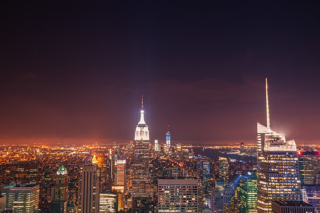 <h2>New York City Skyline - City Lights at Night</h2> - By Vivienne Gucwa   There is nothing like summer nights in the city  when the heavy haze,  thick with the day's dreams,  nestles itself  into the cradle of lights below.  ---  This is a view of the New York City skyline looking south facing the Empire State Building, 1 WTC (also known as the Freedom Tower) and the Statue of Liberty. It is a 25 second long exposure. While this view is probably one of the most popular views in Manhattan, it still never fails to impress.  ---