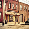 """<h2>Back in Time - Red Hook - Brooklyn - New York City</h2> - By Vivienne Gucwa  There are streets and places that feel as if they have been taken out another time. They seem to exist independently of the world around them as fragments of history that have somehow made it into the present.  Sunny's is a 120 year old saloon that is located in Red Hook, Brooklyn, a neighborhood of New York City that has quite a colorful history. The bar is named after Antonio """"Sunny"""" Balzano who was born in 1934 in the deep red brick apartment right next to the bar. Growing up near the waterfront in Red Hook in the 1940s, he would play alongside ship cargo and after surviving violent street brawls in the 1950s and the crime of the 1980s, he became the owner of the bar that neighbored the apartment where his life unfolded through the years.  The bar was originally run by Sunny's uncle where it revolved around the shipping industry. Longshoremen were the main clientele back then. When Sunny moved back home in the 1980s to take over the operations at the bar, the neighborhood was a shell of what it used to be. The shipping industry had moved its operations across the harbor to New Jersey and for quite a few years the streets remained quiet and Sunny operated the bar just to keep it open for a few neighborhood regulars.   Red Hook has since changed as it has been embraced by both developers, the arts community and families looking to settle down in a quiet part of Brooklyn. Sunny's still exists though, a testament to Red Hook's colorful history.  ---"""