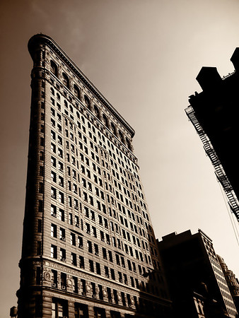 """<h2>The Flatiron Building - New York City</h2> - By Vivienne Gucwa  Out of the shadows, the city rises proudly into the sunlight that casts its glow on the structures borne out of the aspirations and hopes of urban dreamers.  ---  The Flatiron Building (or Fuller Building, as it was originally called) is located on Fifth Avenue in New York City. When its building was completed in 1902, it was one of the tallest buildings in the city. The name """"Flatiron"""" is derived from its resemblance to a cast-iron clothes iron.  ---"""
