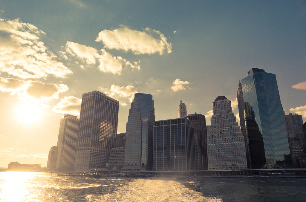 <h2>New York City Skyline - Financial District Skycrapers at Sunset </h2> - By Vivienne Gucwa  There's a series of moments that linger between day and night   that linger a little longer in the summer.   The sun slides down through the clouds towards the city   pouring its soft light onto the water.   The skyscrapers soften their time-worn facades   as they lean in towards the last fragments of the day.   And the spray from the wake of a boat   dances with the sun's light.  ---  This was taken on an absolutely stunning summer evening with the A77 while on a boat in the East River as the boat pulled away from the skyline leaving an illuminated wake behind it. This is the skyline of lower Manhattan in the Financial District. To the right (out of this scene) sits the Brooklyn Bridge.   ---