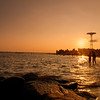<h2>Beach Sunset - Coney Island - Brooklyn - New York City</h2> - By Vivienne Gucwa  The sun whispers to the ocean in golden-voiced tones on evenings like these.  Summer's warmth falls onto the bare skin of the earth as the air is punctuated by the sounds of distant laughter and birds  And the city fades into the haze like a nostalgic thought carried away by an all too familiar melody.  ---