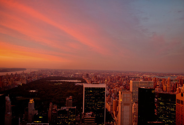 <h2>Sunset Over Central Park and the New York City Skyline</h2> - By Vivienne Gucwa  When the sun stretches its fingers across the surface of the sky, it holds the city in the palm of its hand.   And the sky and the impossible melt away if only for a moment.  ---  Taken from the Top of the Rock (which is located at the top of 30 Rockefeller Center) looking North over Central Park, the eastern part of Manhattan and the skyscrapers of midtown Manhattan.   ---