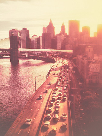 <h2>The New York City Skyline and Brooklyn Bridge at Sunset</h2> - By Vivienne Gucwa  When the last of summer's sun-drenched caresses fall from the sky onto the buildings below, the city swoons and time holds still for a moment wrapped up in the beauty and warmth of this fleeting bliss.  ---  This photo is of a view looking out over the FDR Drive towards the New York City skyline comprised of the the skyscrapers of Lower Manhattan. The Brooklyn Bridge and Pier 17 at South Street Seaport sit in the distance. Taken during a captivating sunset during the peak of summer.  ---