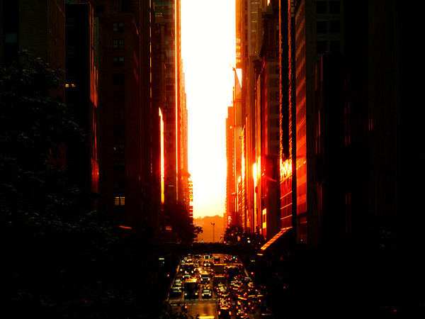<h2>Manhattanhenge Sunset Overlooking 42nd Street and Times Square - New York City</h2> - By Vivienne Gucwa  There is nothing quite like the intensity of seeing the sun spread it's light like wildfire through the streets of midtown Manhattan. The red light glows with the ferocity of a supernova showering its splendor onto the urban landscape.  In honor of tonight's Manhattanhenge sunset which may or may not be hidden by storm clouds since New York City's weather has been highly unpredictable and stormy as of late, this is a photo I took exactly a year ago during last year's Manhattanhenge. The buildings in this photo are the buildings in Times Square (you can make out the Madame Tussauds sign).  Manhattanhenge is a semiannual occurrence in which the setting sun aligns with the east–west streets of the main street grid in the borough of Manhattan in New York City. The term is derived from Stonehenge, at which the sun aligns with the stones on the solstices. It was coined in 2002 by Neil deGrasse Tyson, an astrophysicist who is the director of the Hayden Planetarium at the American Museum of Natural History.  ---
