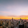 <h2>New York City Sunset - Skyline </h2> - By Vivienne Gucwa  I never really get tired of this view.   I know I have expressed that sentiment many times but it's absolutely true. There's something incredibly breathtaking that occurs when you are above the rooftops of the city. It's as if the city shrinks below a vast sky in a huge universe and everything that once seemed impossible seems effortless and within the realm of possibility.   It's so easy to forget that sort of thing when you live in a large city like New York City. When you are in the thick of it all, it can feel like the you are alone in a never-ending maze of cavernous streets as everyone else's dreams and hopes fly past you at the speed of light. But when you take yourself out from the middle of everything and change your perspective, it's as if the city holds its arms out to you beckoning you to come back and put your own dreams out there so they can spread their wings and fly up to the sky towards the horizon leaving a trail of hope in their path.    ---  This was taken from the top of Rockefeller Center (also known as Top of the Rock) and it's probably one of the most popular views of the New York City skyline since it includes the Empire State Building and the skyscrapers of midtown Manhattan. The view is looking south towards One World Trade Center (also known as the Freedom Tower and 1 WTC) and the skyscrapers of the Financial District.   ---