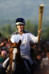 Zara Phillips carries the Olympic torch whilst riding her horse Toytown at Cheltenham Racecourse June 2012