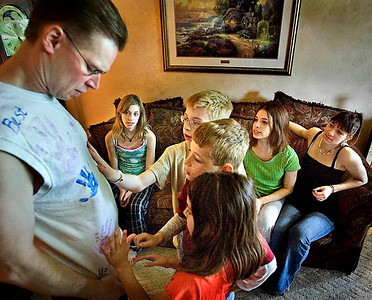 Annie Kerr, 13, Aubrey, 17, and Alyssa, 15, watch as their younger siblings, from top down, Alex, 10, Andrew, 9, and Alexis, 7, put their hands on their hand prints on a shirt made by all of the children in 2006 as a father's day gift for their father, Jon, as they talk about their family in their Sheboygan home on Friday, June 13, 2008. Not pictured are the two youngest children, Allison and Ava. Photo by Sam Castro/The Sheboygan Press