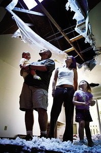 Craig and Katie Thimm and their daughters Mykenzie, 10 months, and Mykayla, 3, look through the hole that used to be the ceiling in their living room in their Roosevelt Drive apartment building in West Bend. The fire was a result of a grill that was used on their neighbor's porch.