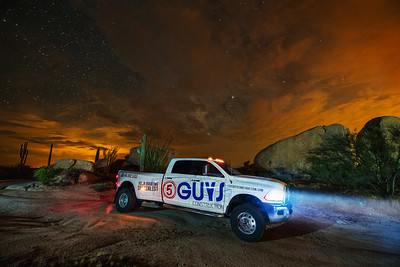 5 Guys Constructions Truck Under Clouds and Stars with Saguaro Cactus and Boulders