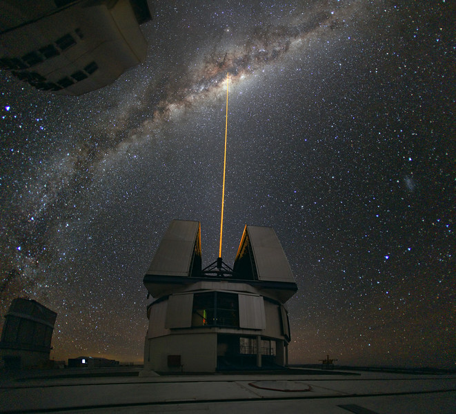 Very Large Telescope, Cerro Paranal. Photo by Yuri Beletsky.  A group of astronomers were observing the centre of the Milky Way using the laser guide star facility at Yepun, one of the four Unit Telescopes of the Very Large Telescope (VLT). Yepun's laser beam crosses the majestic southern sky and creates an artificial star at an altitude of 90 km high in the Earth's mesosphere. The Laser Guide Star (LGS) is part of the VLT's adaptive optics system and is used as a reference to correct the blurring effect of the atmosphere on images.  The colour of the laser is precisely tuned to energise a layer of sodium atoms found in one of the upper layers of the atmosphere — one can recognise the familiar colour of sodium street lamps in the colour of the laser. This layer of sodium atoms is thought to be a leftover from meteorites entering the Earth's atmosphere. When excited by the light from the laser, the atoms start glowing, forming a small bright spot that can be used as an artificial reference star for the adaptive optics. Using this technique, astronomers can obtain sharper observations. For example, when looking towards the centre of our Milky Way, researchers can better monitor the galactic core, where a central supermassive black hole, surrounded by closely orbiting stars, is swallowing gas and dust.