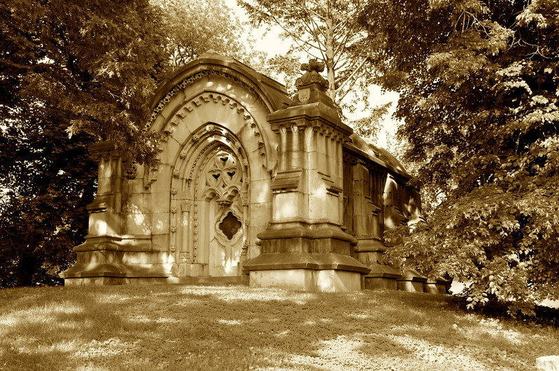 "May 31, 2011 Daily Photo. Taken on 5/29/11.<br /> <br /> This massive Mausoleum is located in The Green-Wood Cemetery in Brooklyn, tucked away behind large trees. I find it unusual in that it has no names anywhere on it. You can see the letter ""M"" on the top of the front columns, although one is not visible in this photo. The front door has a screen rather than glass and the small windows in the stone above the door are also missing glass. I'm guessing this is about 150 years old based on the architecture and condition. Green-Wood opened in 1838 and was and remains a favorite resting place of the elite."