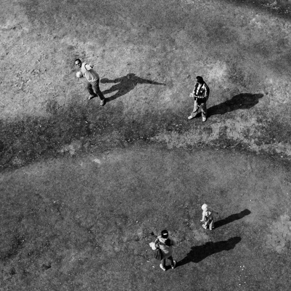 Taken from the top of Leith Hill tower, family playing a ball game, lots of shadows so B&W.