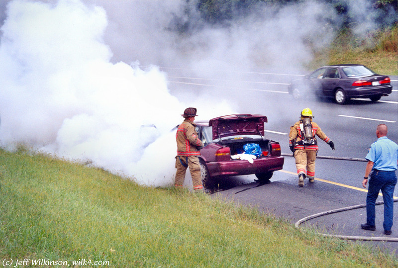 a car fire I stopped to help with one day... here are the pro's in action!<br /> (I am *not* a pro firefighter obviously) - (scan from film print)