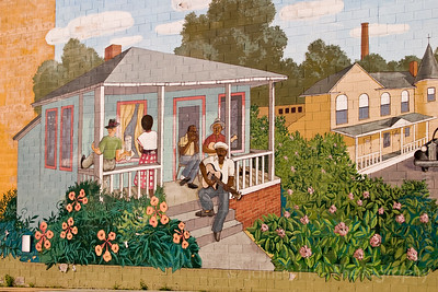 This is John Dee Holeman sitting on his front porch playing and singing some blues.  John still lives just up the road from the mural.