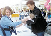 "jhbachelor1 - Bob Guiney (right) who started in ABC's ""The Bachelor"" has a panicked look as Wendy Baird of Brighton hands her baby Margaret, 4 months old, to the former star for a photograph during an autograph session at Eastview Mallon Saturday  to help raise money for the Golisano Children's Hospital at Strong."
