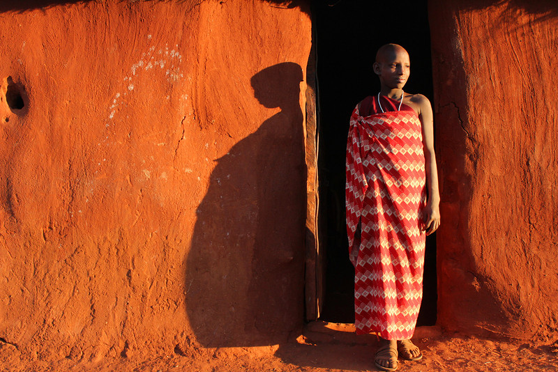 A young Maasai woman asks for her portrait outside her home inside the boma.