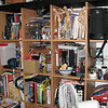 "Day 3  Holy Moly! my place is messy. Well yes, yes it is - but as they say: ""Messy IKEA Expedit</a> bookcase - clean mind"" .. er.. or something like that. In any case this photo is really case closed - if you want to work out what or who I am - check out the bookcase, nearly everything I have ever been into is on a shelf somewhere.   I wish I could annotate this flickr style - but you'll just going to have to believe me I guess =).  Wrox press, combined with CCNA guides, Watchmen comic , a Sigma 180mm F3.5 Macro (excellent lens btw), heaps of drawing & painting stuff and a bunch of posable figurines that are about to throw themselves off the bookcase, yes, it's all about there."