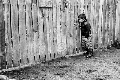 A boy peeks through a fence in the village of Ushguli in Svaneti, Georgia, part of a recognized UNESCO World Heritage Site. Located at an altitude of 2,100 meters near the foot of Shkhara, one of the highest summits of the Greater Caucasus mountains, Ushguli is one of the highest continuously inhabited settlements in Europe. It is home to 70 families and covered in snow for 6 months of the year. Often the road to Mestia is impassable. Ushguli shares the Svaneti region traditional koshki, defensive stone structures built from the 9th century onward and is known for it's architectural treasures and picturesque landscapes.