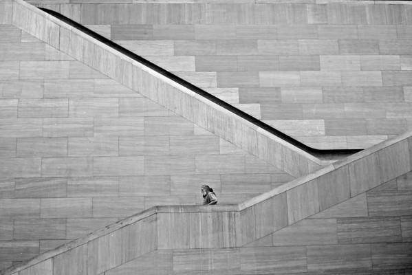 A man walks down the steps at the Museum of Modern Art.