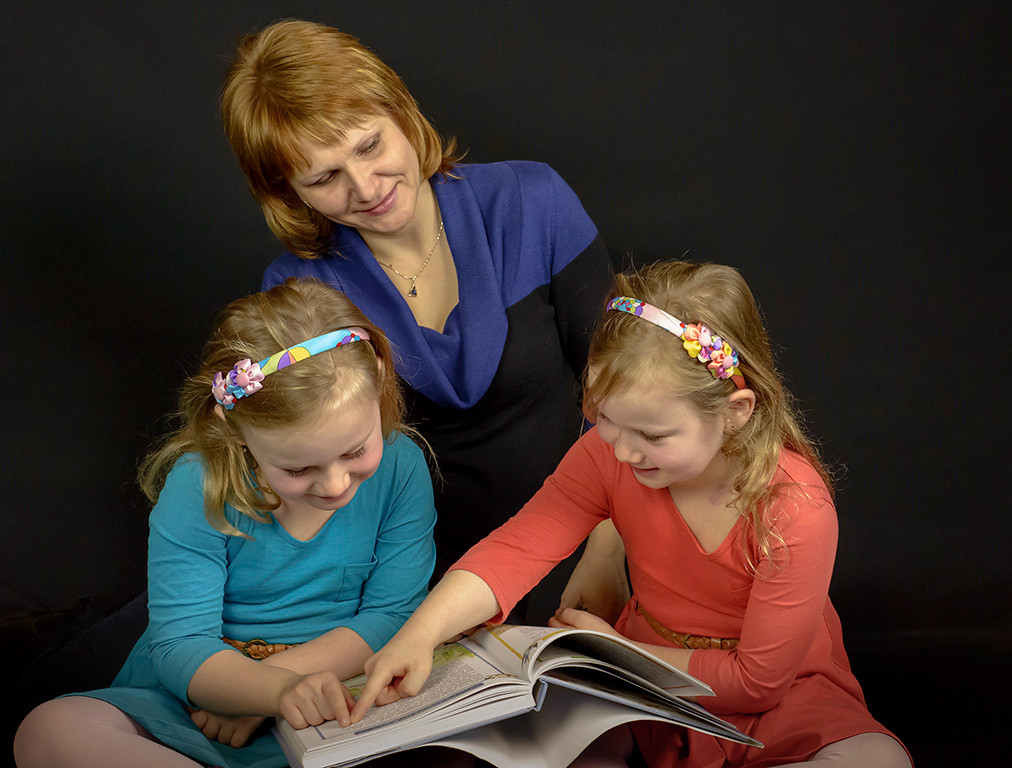 A mother and her daughters gathered around a book.
