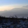 Desert dust softens the landscape at dusk.
