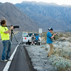 Photo by Glen Nakasako.  Mark Bowen (foreground with yellow shirt) and Kent Sweitzer (right in blue shirt) check the light for photographs of windmills in the blowing sand.