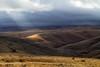 A solar spotlight shines on the hills of northeastern Oregon east of Heppner.<br /> Photo © Carl Clark