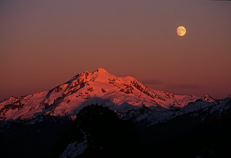Glacier Peak is bathed in alpenglow as the moon rises - Washington Cascades.<br /> Photo © Carl Clark