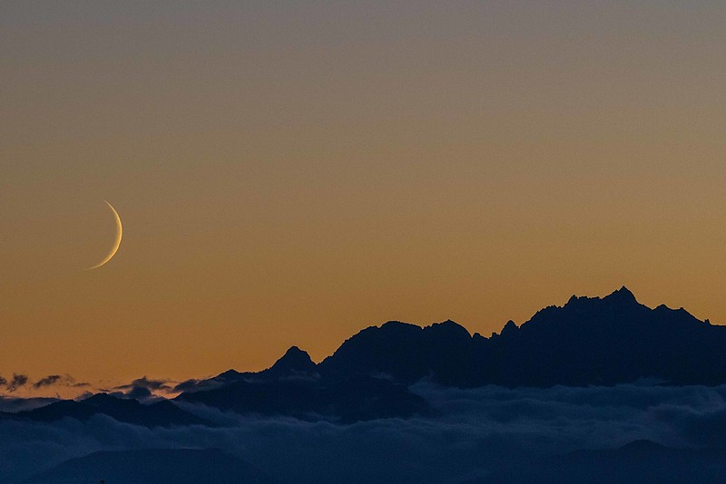 A sliver of moon setting behind Mt Constance in the Olympic Mountains.<br /> Photo © Carl Clark