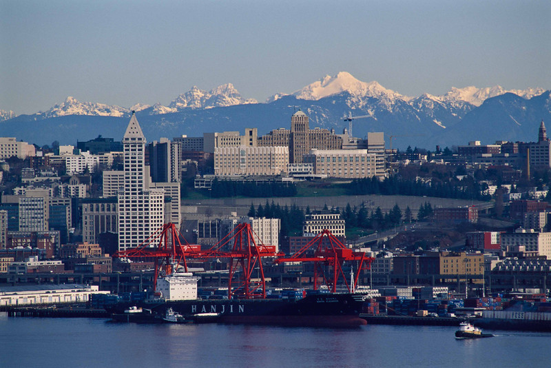 A working waterfront.  Seattle with the historic Smith Tower in the foreground.  Glacier Peak dominates the mountains behind.<br /> Photo © Carl Clark