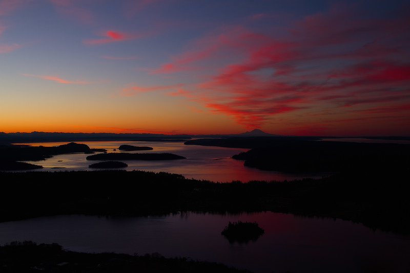 Islands dot the water with Mt Rainier in the distance in a sunrise view from Mt Erie.<br /> Photo © Carl Clark