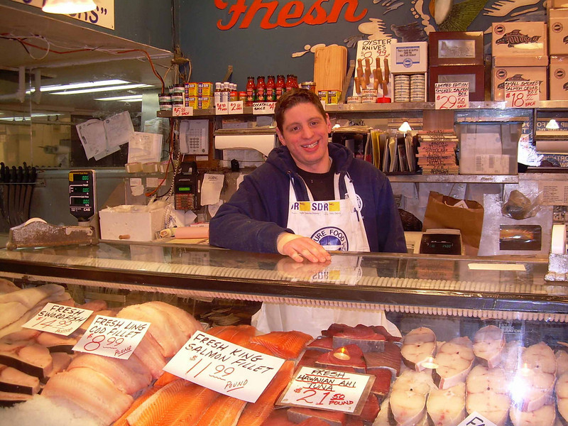 Neal Brebner enjoying his day at Pure Food Fish Market in Pike Place Market in Seattle.<br /> Photo © Carl Clark