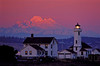 Mt Baker is bathed in alpenglow behind the Pt Wilson lighthouse near Port Townsend.<br /> Photo © Carl Clark