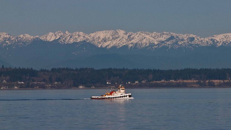 A tugboat steams before the Olympic Mountains.<br /> Photo © Carl Clark